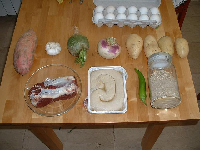 twelve eggs, a sweet potato, a head of garlic, some kind of green turnip, a regular turnip, four potatoes, a cut of meat, a kishke, a chilli pepper, and a jar of wheat grains